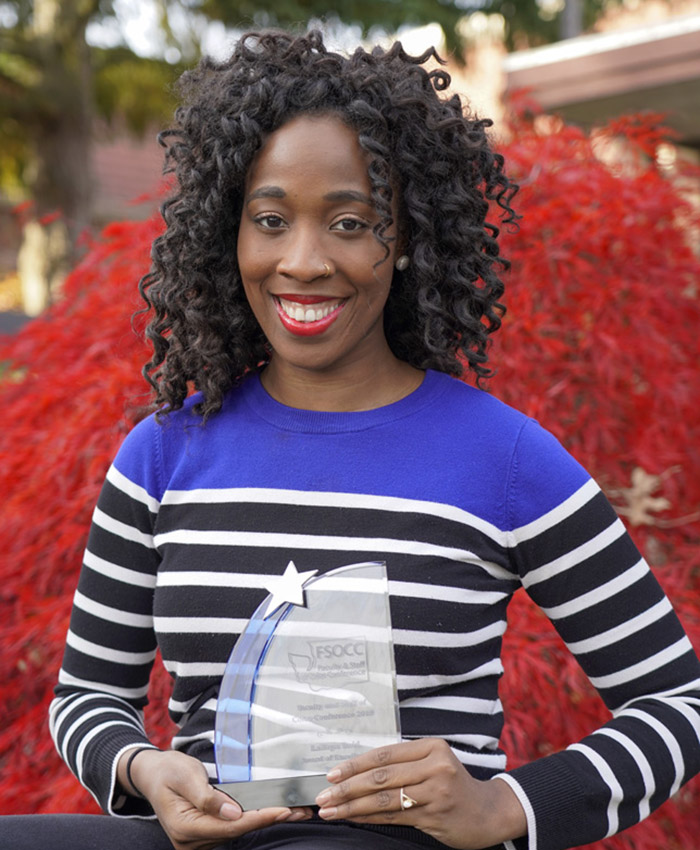 Photo of Latoya Reid holding an award in front of a tree near Building F1 at TCC.
