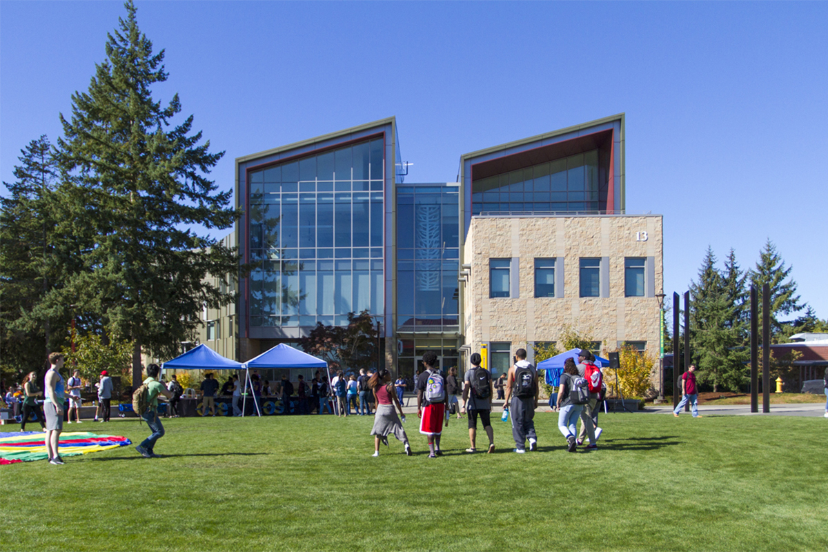 Students walking across the campus commons toward building 13